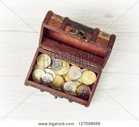 Retro wooden money chest filled with coins. Wealth theme. Saving money.