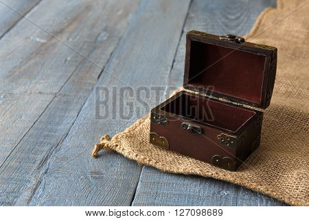 Wooden chest or trunk vintage style. Open Wooden chest box on sackcloth at serenity colored wooden plank table background. With copyspace.