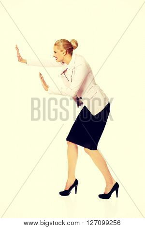 Attractive business woman pushing something
