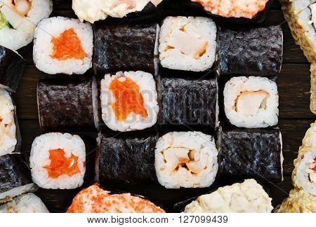 Japanese food background - sushi maki gunkan salmon roll at wooden background, above view. Closeup detail of sushi rolls. Sushi set macro close up.