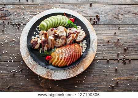 Food photography of baked veal with fresh fruits on wooden background. Baked meat with tropical fruits top view. Flat lay of creative food from baked veal on wooden table.