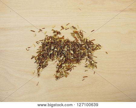 Loose green rooibos tea on wooden bard