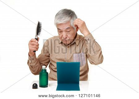 studio shot of senior Japanese man using hair restorer on white background