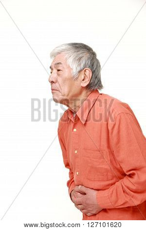 portrait of senior Japanese man suffers from stomachache on white background