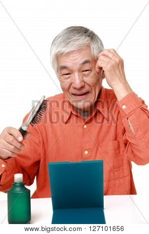 senior Japanese man using hair restorer on white background