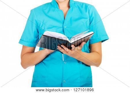 Young female doctor or nurse holding black notes