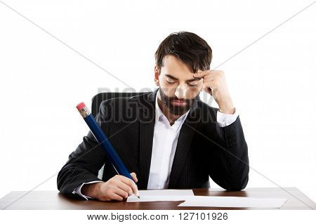 Tired businessman writing in the office