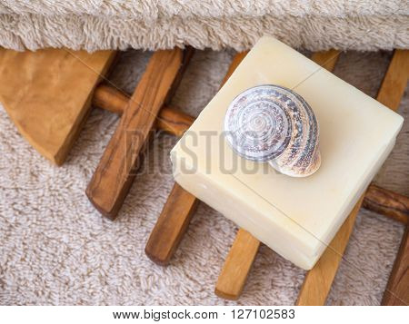 Natural soap bar snail shell and terry towel on the olive tree textured wooden lattice