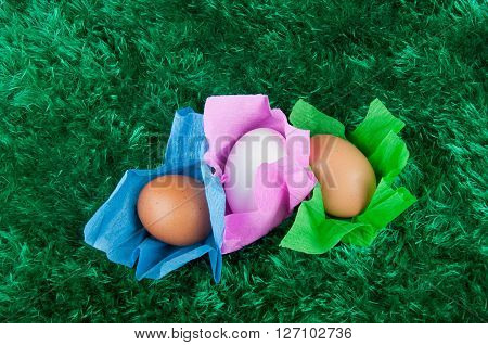 beige brown white chicken eggs in colored green blue pink paper wrapper on green grass background