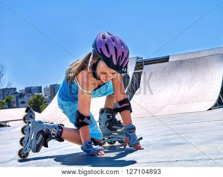 Girl riding on roller skates in skatepark.