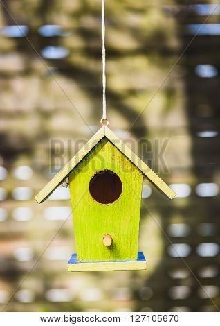 An old weathered DIY birdhouse hanging from the tree. Colorful small bird house with green walls.