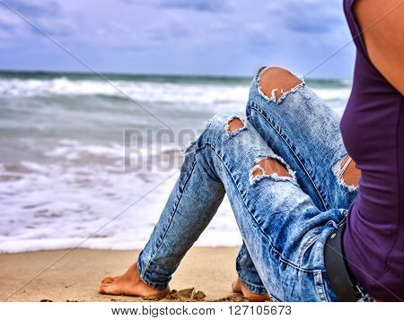 Legs of woman sitting on coast near ocean with waves. Hot dog leg selfie.