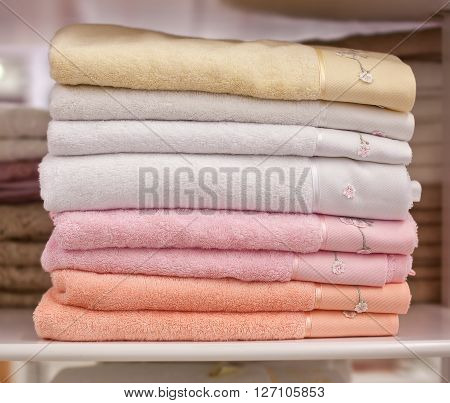 Pile colored of terry towels on the shelf.