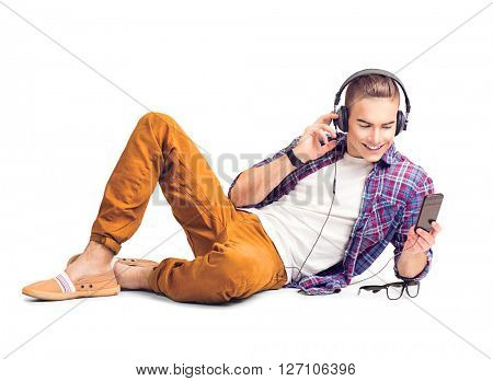 Handsome young hipster man lying on the floor listening to music with smart phone. Handsome young stylish man in headphones with smartphone, isolated on a white background