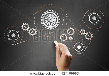 Man drawing gears on blackboard