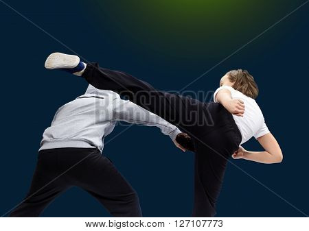 In sports pants girl beats robber on the blue background