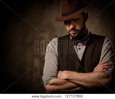 Serious old-fashioned man with hat posing on dark background.