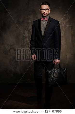 Well-groomed stylish young man with briefcase posing on dark background.