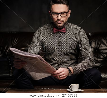 Confident handsome bearded man with newspaper sitting on comfortable leather sofa on dark background.