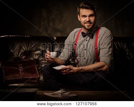 Young handsome old-fashioned bearded man with cup of coffee sitting on comfortable leather sofa on dark background.