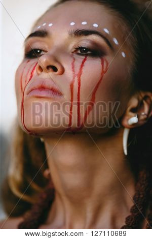 Portrait of a female crying with a tear of blood