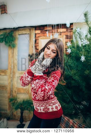 Young girl near a fur-tree by New year with gifts