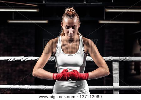 Young athlete woman showing her fists with bandage ready for fight eyes closed. Close up boxer female on uniform stands in the ring and getting ready to box.