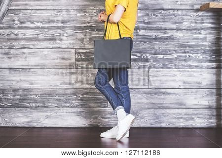 Sideview of female body with blank shopping bag on wooden background. Mock up
