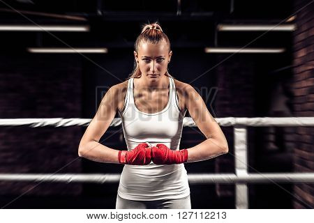 Young athlete girl boxer showing her fists with bandage ready for fight. Close up boxer female on uniform stands in the ring and getting ready to box.