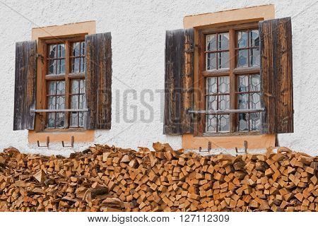 old farmhouse front with lattice windows and stacked firewood