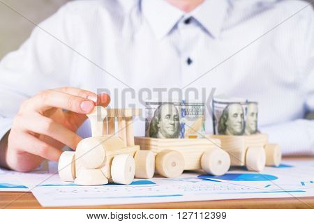 Frontview of male hand with wooden toy train filled with dollar banknotes