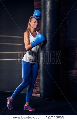 Healthy young woman leaning against a punch bag wearing blue boxing gloves. Beautiful fair-haired girl in boxing gloves, leaning on the black punching bag, smilling, posing for a camera.