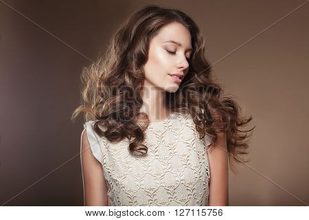 Sensual young woman with beautiful long brown flying hairs.