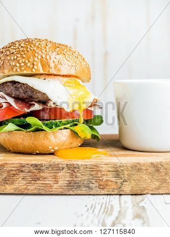 Breakfast set. Homemade beef burger with fried egg and vegetables, onion rings and coffee cups on wooden board, white painted background. Selective focus
