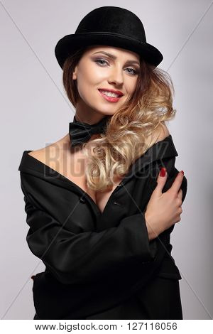 Young cute woman in bowler hat smiling.
