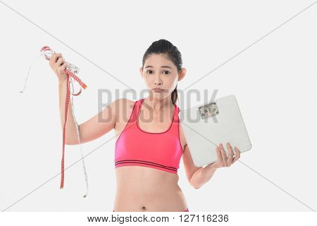 Young asian woman holding scales with a tape measure