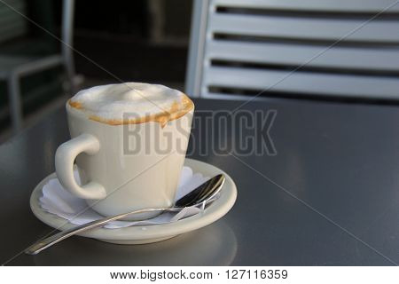 Cappuccino in plain white cup on table at restaurant.