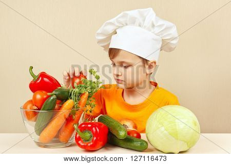 Little kid in chefs hat chooses vegetables for salad at the table