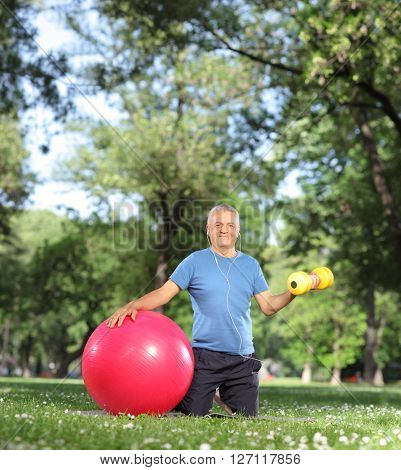 Mature man exercising in park with a yellow dumbbell and a fitness ball shot with tilt and shift lens