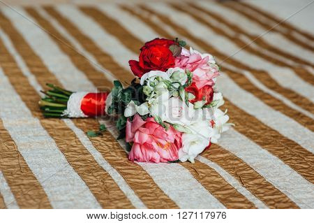 Bridal Bouquet Of Roses On The Bedspread
