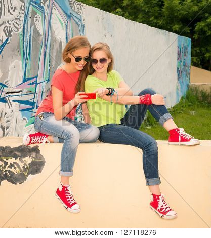 Friendship technology and internet concept - two smiling teenage girls with smartphone outdoors. Teenagers chatting and laughing using smart phone near urban wall.