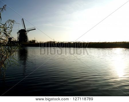 Traditional Dutch Windmill Near The Canal With Late Afternoon Sunlight. Netherlands