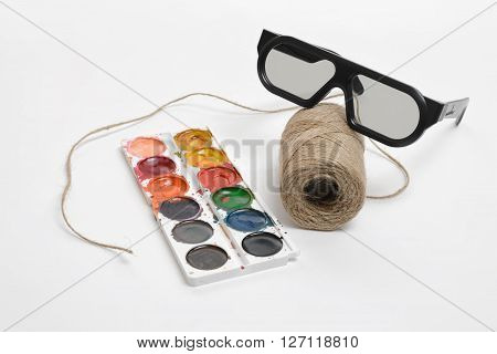 Top view of art scene featuring of thread twine, glasses and watercolor paints on a white background. Equipment of art designer.