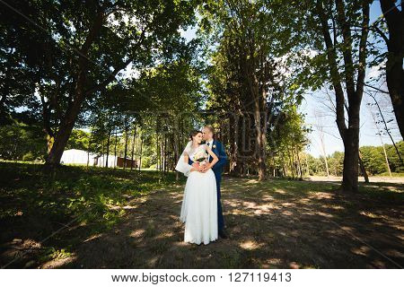 Beautiful brunette bride in elegant dress and handsome groom in blue suit at wedding day lovely hugging on nature outdoors. Bridal couple embracing in green park. Loving wedding couple.