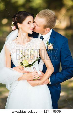 Beautiful brunette bride in elegant dress and handsome groom in blue suit at wedding day lovely hugging outdoors on nature. Loving wedding couple. Happy newlywed woman and man embracing in park.