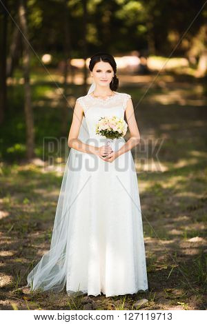 Beautiful sensual young brunette bride in veil and white wedding dress standing in forest holding bouquet outdoor on natural background. Magic photo