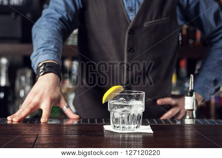 This is closeup of Barman serving cocktail.