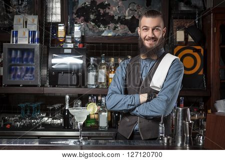 Happy barman at work with crossed hands.