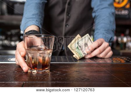 Barman giving whiskey glass with booze - closeup.