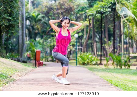 Asian Woman stretching in fitness exercise or sport training in tropical park